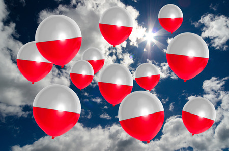 many balloons in colors of poland flag flying on sky