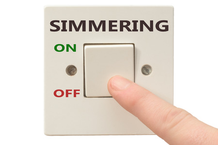 spiritual growth: Turning off Simmering with finger on electrical switch Stock Photo