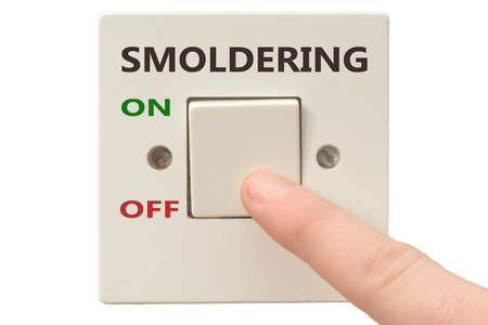 smoldering: Turning off Smoldering with finger on electrical switch Stock Photo
