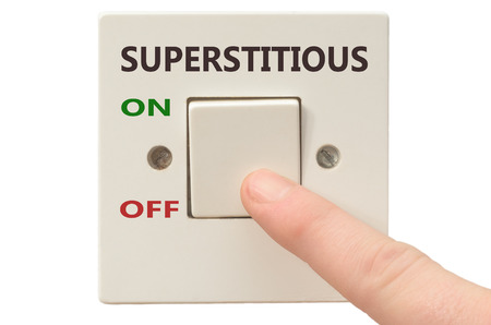 superstitious: Turning off Superstitious with finger on electrical switch Stock Photo