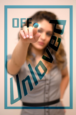 unloved: young woman turning off Unloved on hologram screen Stock Photo