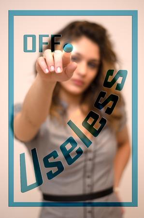 useless: young woman turning off Useless on digital panel Stock Photo