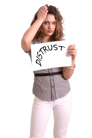 desconfianza: Papel que sostiene la mujer atractiva joven con el texto La desconfianza en el fondo blanco Foto de archivo