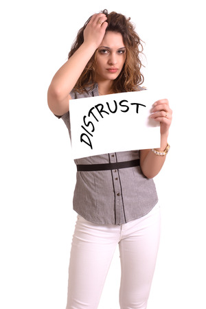 distrust: Young attractive woman holding paper with Distrust text on white background Stock Photo