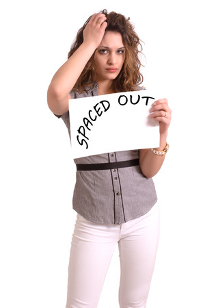 apathy: Young attractive woman holding paper with Spaced out text on white background Stock Photo