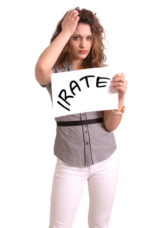 irate: Young attractive woman holding paper with Irate text on white background Stock Photo
