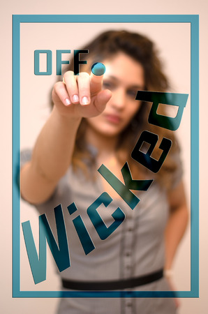 wicked woman: young woman turning off Wicked on screen Stock Photo