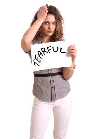 tearful: Young attractive woman holding paper with Tearful text on white background