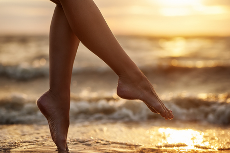 natural summer background. woman legs on beach Banco de Imagens - 68690680