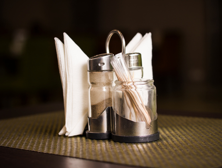 Pepper shaker, salt shaker and napkins on a stand on a table Stock Photo