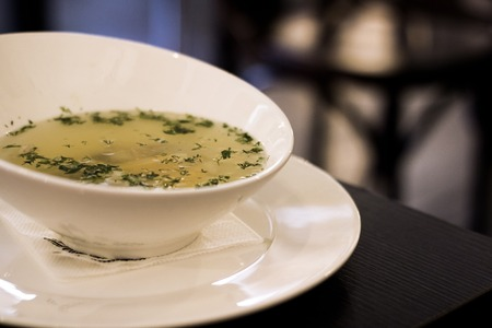 Chicken broth with herbs on a wooden table, healthy food Фото со стока