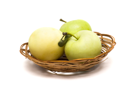Three green apples in a basket on a white background,