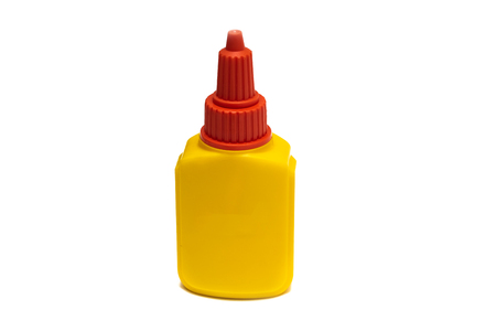 Yellow container with glue close up, isolate on a white background
