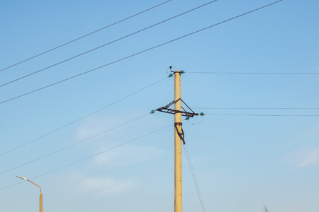 A pole with electric wires against a blue sky, copy space