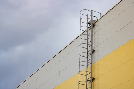 Ladder to the roof of a tall building on a dark sky background, copy space