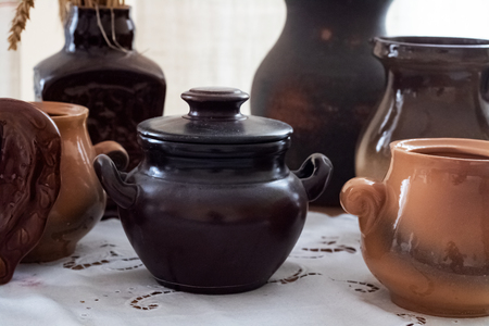 Brown clay pots on a table close up, old dishes