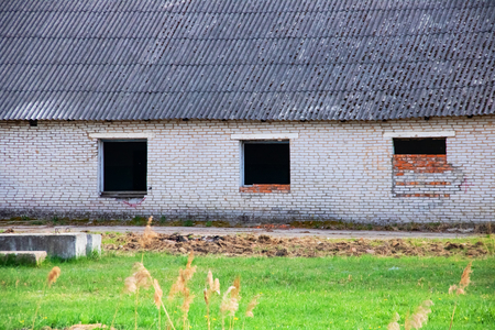 The windows of the old destroyed industrial brick building and green grass