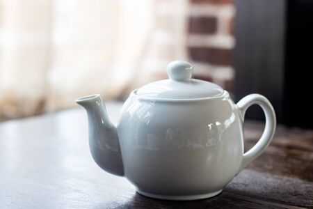 White teapot with tea on a wooden table