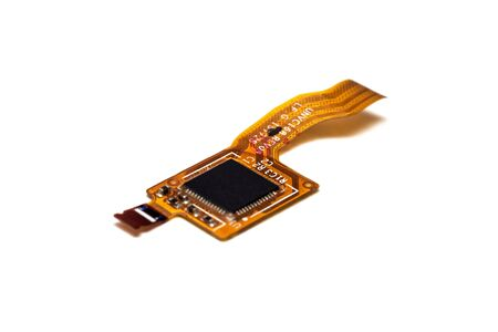 Small microcircuit and orange ribbon cable, isolated