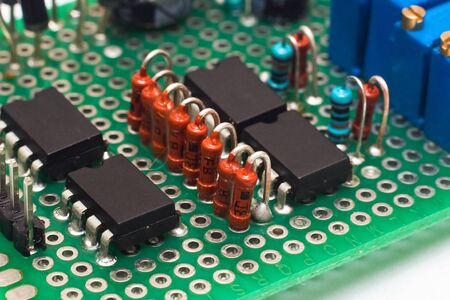 Green PCB with transistors close up on white background