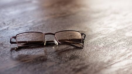 Glasses on a wooden table close up, the sun's rays from the window
