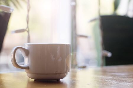 White cup of coffee on a wooden table on a window background
