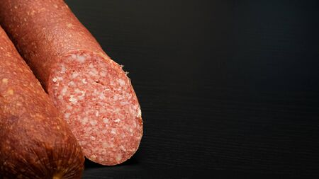Smoked salami sausage on black wooden table copy space