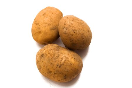 Three raw fresh potatoes isolated on a white background