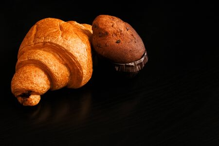 Ruddy croissant with chocolate and cupcake on a black wooden table Archivio Fotografico - 131706006