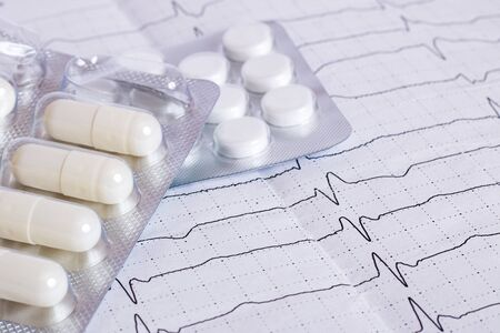 Cardiogram results on paper and pills, heart health Banco de Imagens
