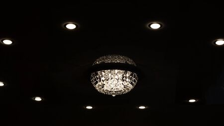 Large retro glass chandelier on the ceiling in the dark 写真素材