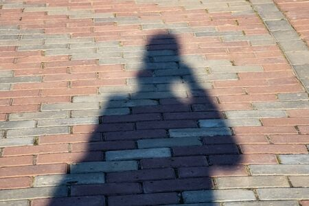Shadow of a man on the sidewalk of tiles close up 版權商用圖片