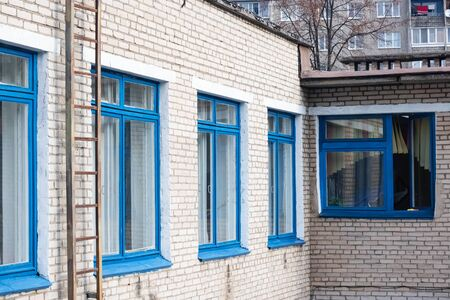 Blue windows of a brick building and a staircase to the roof