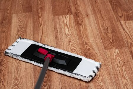 White mop washes wooden floor close up, copy space