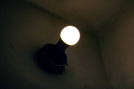 Light of an old light bulb on a wall in the dark close up