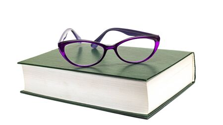 Glasses on a green thick book isolated on white background Foto de archivo - 133510009
