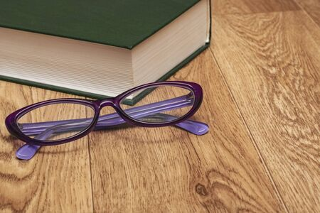 Glasses and a green thick book on a wooden table Foto de archivo - 133510010