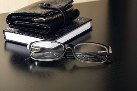 Glasses, wallet and notebook on a wooden table close up 写真素材
