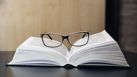 Glasses on an open book on a wooden table close up