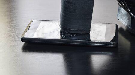 Broken screen telephone with heel shoes close up 写真素材
