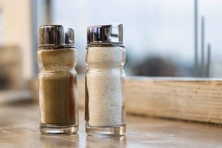 Salt shaker and pepper shaker on a wooden table