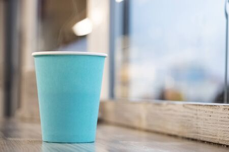 Blue paper cup with coffee on a wooden table, copy space