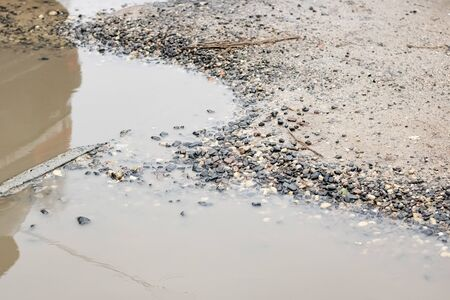 Yellow puddle with sand and stones close up
