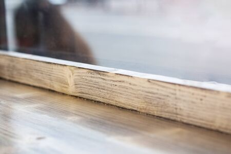 Wooden window sill and glass close up, background