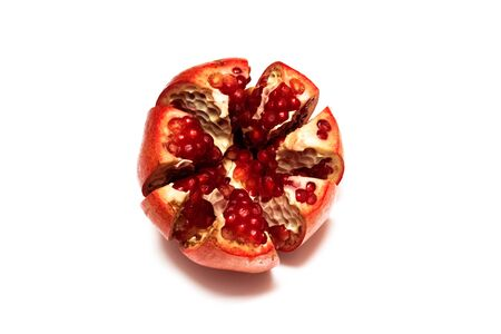 Sliced pomegranate with red grains, isolated on a white background