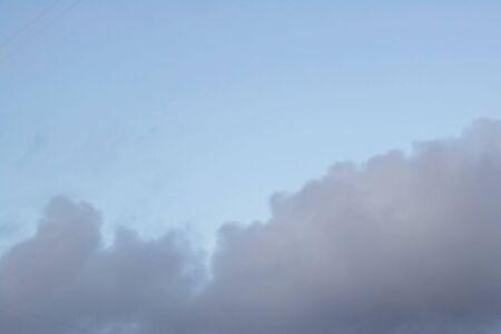 Dark sky with blue clouds close up, blurred background 写真素材