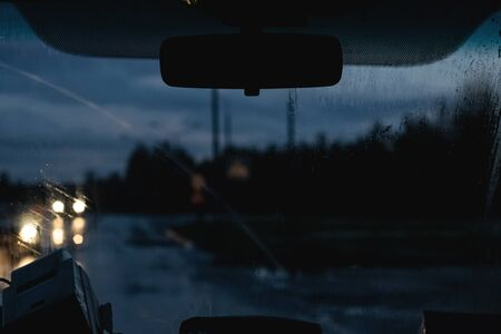 Car front window with raindrops and road with cars at night