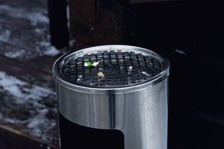 Rubbish bin smoking area on the street