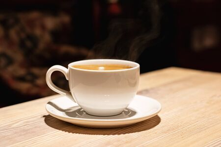 Cup with aromatic coffee on a wooden table in the evening 版權商用圖片