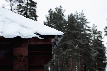 Snow on the corner of the roof of a house in the forest close up